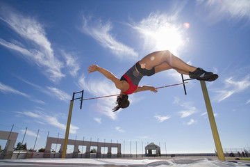 Female athlete jumping over bar, low angle view (lens flare)