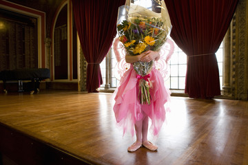 Ballerina girl (10-12) obscuring face with bunch of flowers onstage