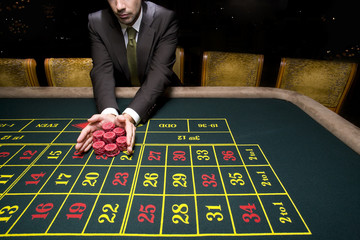 Man pushing pile of chips on roulette table