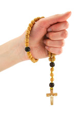Female hand holds wooden rosary