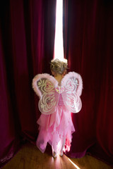 Girl (4-6) with fairy wings looking out gap in curtains, rear view