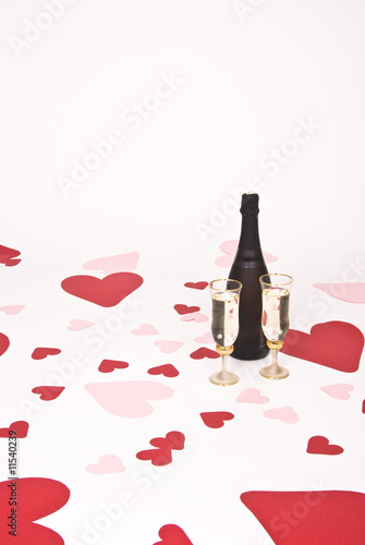 two glasses  of white wine on white heart covered background