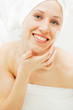 young smiley woman with face cream after shower