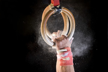 Male gymnast performing on gymnastic rings, close-up of hands