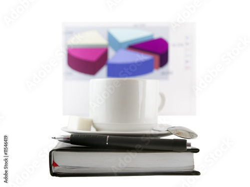 Coffee, standing on organizer, and  diagrams .Focus at the pen
