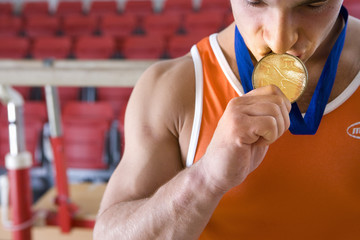 Male gymnast kissing gold medal around neck, close-up