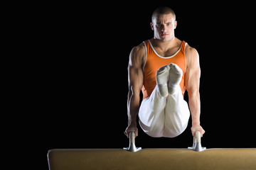 Male gymnast performing on pommel horse, portrait
