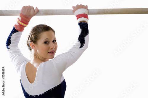 Female gymnast with hands on bar, smiling, portrait