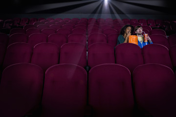 Couple in empty cinema with drink and popcorn