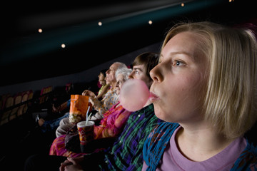 Audience in cinema, woman blowing bubble with gum, side view