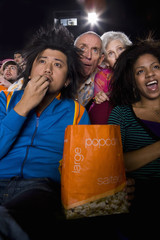 Audience in cinema, man with popcorn, close-up, low angle view