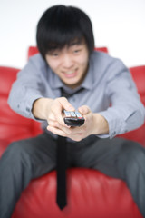 The smiling young man in a grey shirt watches TV