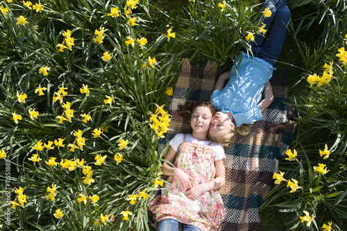 Two young girls laying in field of daffodils
