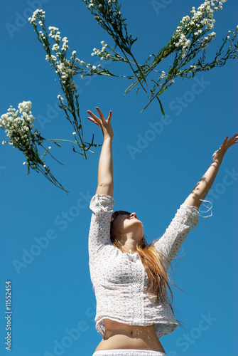 The girl throwing up a bunch of flowers against  sky