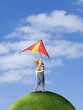 Boy flying kite on top of grassy globe