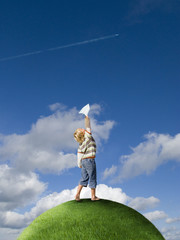 Boy throwing paper airplane on top of grassy globe