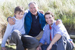 Portrait of multi-generation family crouching on beach