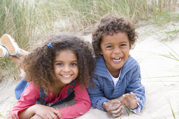 Portrait of two children lying on beach
