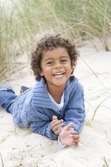 Portrait of boy lying on beach