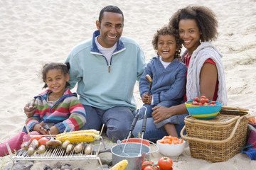 Portrait of family preparing barbecue on beach