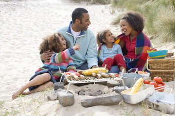 Family preparing barbecue on beach