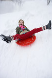 Young girl sledding down snow slope