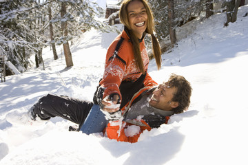 Mixed race couple playing in snow