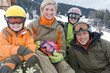 Portrait of young family in ski gear sitting in snow