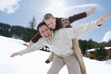 Father and son playing in winter setting