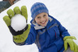 Portrait of young boy holding snowball