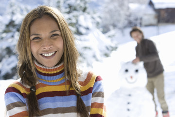 Portrait of young mixed race woman in winter setting, man with snowman in background