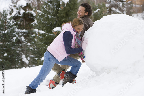 Playful couple rolling huge snowball for snowman