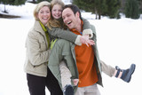 Young happy family standing in snow