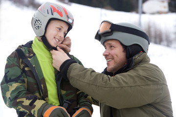 Father helping son with ski helmet