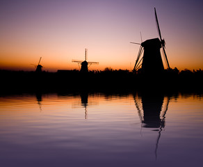 Dutch windmills in the sunset with reflection on the water