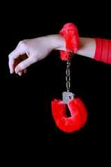 Pink soft handcuffs isolated on black