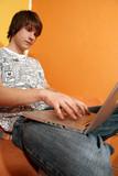 Boy relaxing on sofa in livingroom using laptop for internet poster