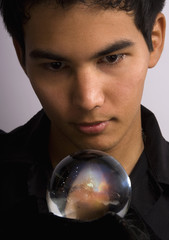 Asian American man stares into a crystal ball to see the future