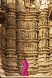 Tourist looking at erotic temple carvings at Khajuraho, India poster