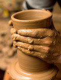 Close up of hands of the potter creating utensils poster