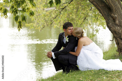 Newlywed couple kissing by lake