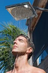 Man Under Outdoor Shower Head and Shoulders