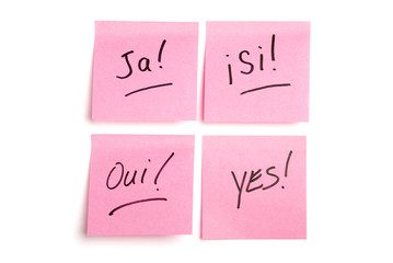 Four pink postits in four languages