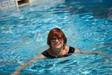 Active senior woman swimming poster