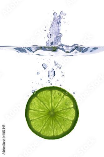 Lime slice falling into the water on white background