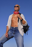 Handsome mature man adventurer posing with a backpack outdoors poster