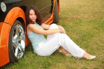 Girl sits on grass near car