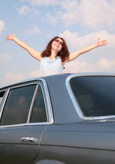 Girl with raised hands and car