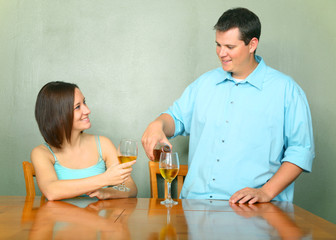 Young Couple Enjoying Wine On Kitchen Table