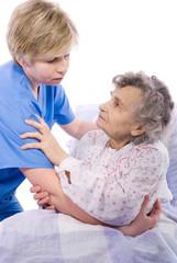 nurse helps the senior woman get up